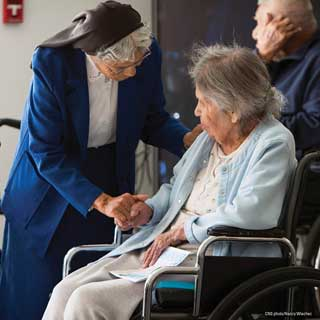 Nun assisting elderly woman in a wheel chair