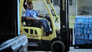 Man using a forklift to move a pallet of bottled water at Catholic Charities of Shiawassee and Genesee Counties