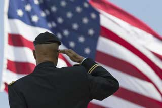 Soldier saluting an American flag waving in the wind
