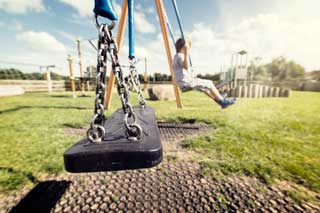 Empty swing in a children's playground, with a lone child in the background