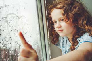 A young girl draws a heart in the raindrops that have collected on a window