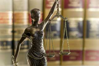 A statue of Lady Justice stands in front of a row of legal books