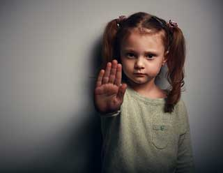 A small child holds her hand up to the camera, imploring the viewer to stop