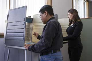 A man and a woman both exercising their right to vote