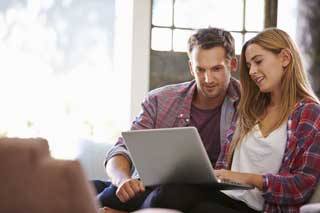 A man and a woman working together on a laptop while sitting on the couch at home