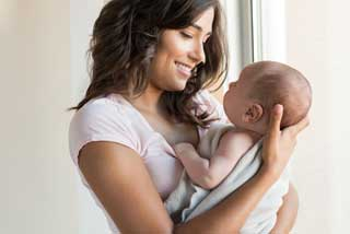 A young mother holding her infant and smiling