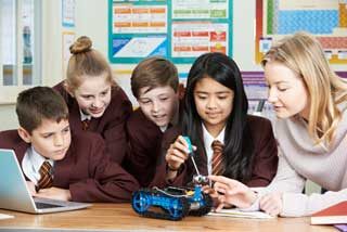 Four students and their teacher work together to assemble a robot