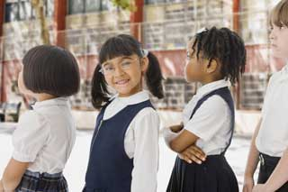 Four school children, one of whom is smiling at the camera