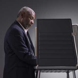 A man casting his vote in a voting booth