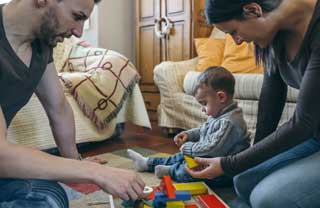 A young boy and his parents play with building blocks on their living room floor