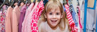A young girl smiles as she peeks out from between several items of clothing hanging on a rack