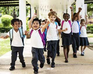 A group of Catholic school children, outside, laughing and running towards the viewer