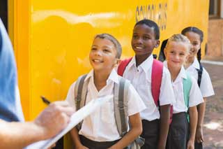A group of smiling school children standing in line to board a school bus