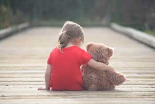 A little girl sits on a wooden walkway with her arm around a teddy bear
