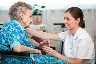 A young nurse smiles at an elderly woman in a wheelchair while handing her a glass of water
