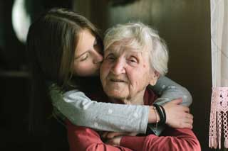 A young girl kissing a smiling elderly woman on the cheek