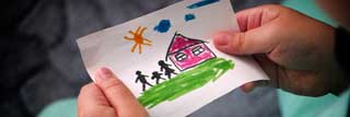 A young child's hands holding a drawing of a house and family