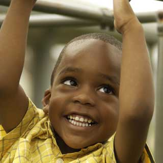 An African-American boy smiles while playing at a playground