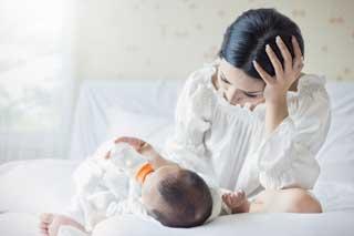An overwhelmed mother bottle-feeding her newborn baby
