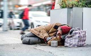 A destitute man sleeping on the sidewalk