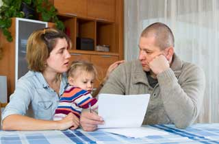 A young mother and father hold their small daughter while figuring out their financial situation
