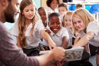 A teacher and group of smiling schoolchildren work on their reading lessons