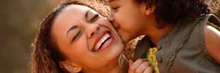 A smiling mother being kissed on the cheek by her young daughter