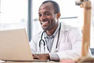 A smiling doctor reviews patient records on his computer