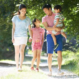 A smiling mother and father and their two children walk along a nature trail