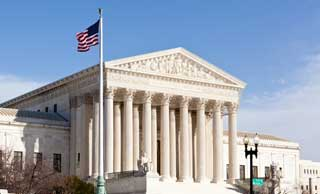The flag of the United States flying over The Supreme Court building in Washington, DC