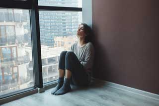 A depressed woman sitting against the wall in her apartment