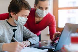 A student and teacher wearing masks, working together to solve a problem on a laptop