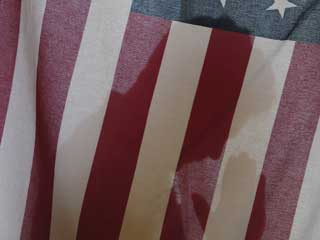 The silhouette of a man praying behind an American flag