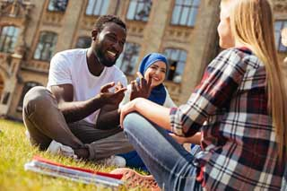 A group of three young people discussing politics while sitting outside