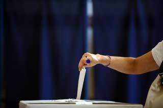 A woman's hand inserting her ballot into a ballot box