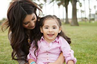 A mother smiles at her daughter, holding her on her lap in a park