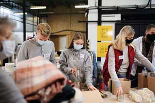 A group of volunteers wearing face masks working at a food bank and donation center