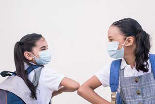 Two school girls wearing protective face masks bump elbows