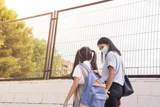 A young girl and her mother wearing protective face masks and walking hand in hand to school.
