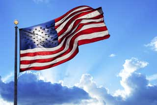 The American flag waving in the wind while the sun breaks through the clouds behind it