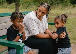 A mother and her two children sitting on a park bench.