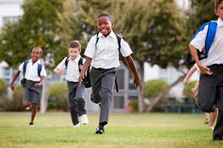 Five smiling children wearing school uniforms running in the grass