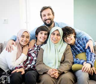 A happy Muslim family poses for a portrait on the sofa