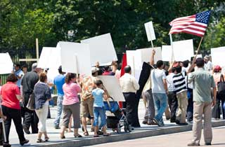 People marching, carrying protest signs, and waving an American flag