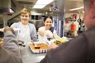 Two staff serving food in a homeless shelter kitchen