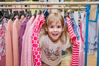 Happy child peaking through a clothing rack