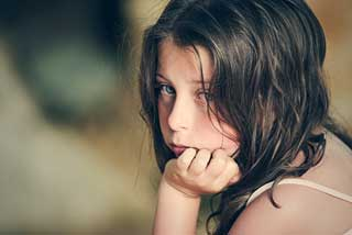Young girl staring forlornly at the camera