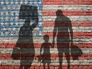 Silhouette of immigrant family on a weathered brick wall painted with the American flag
