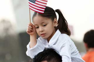 Young immigrant girl waving an American flag while riding on her father's shoulders
