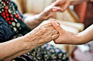 Close-up of an elderly person's hands being clasped in those of a younger person